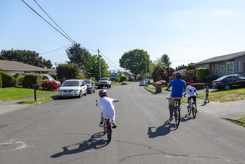 family biking on an open street